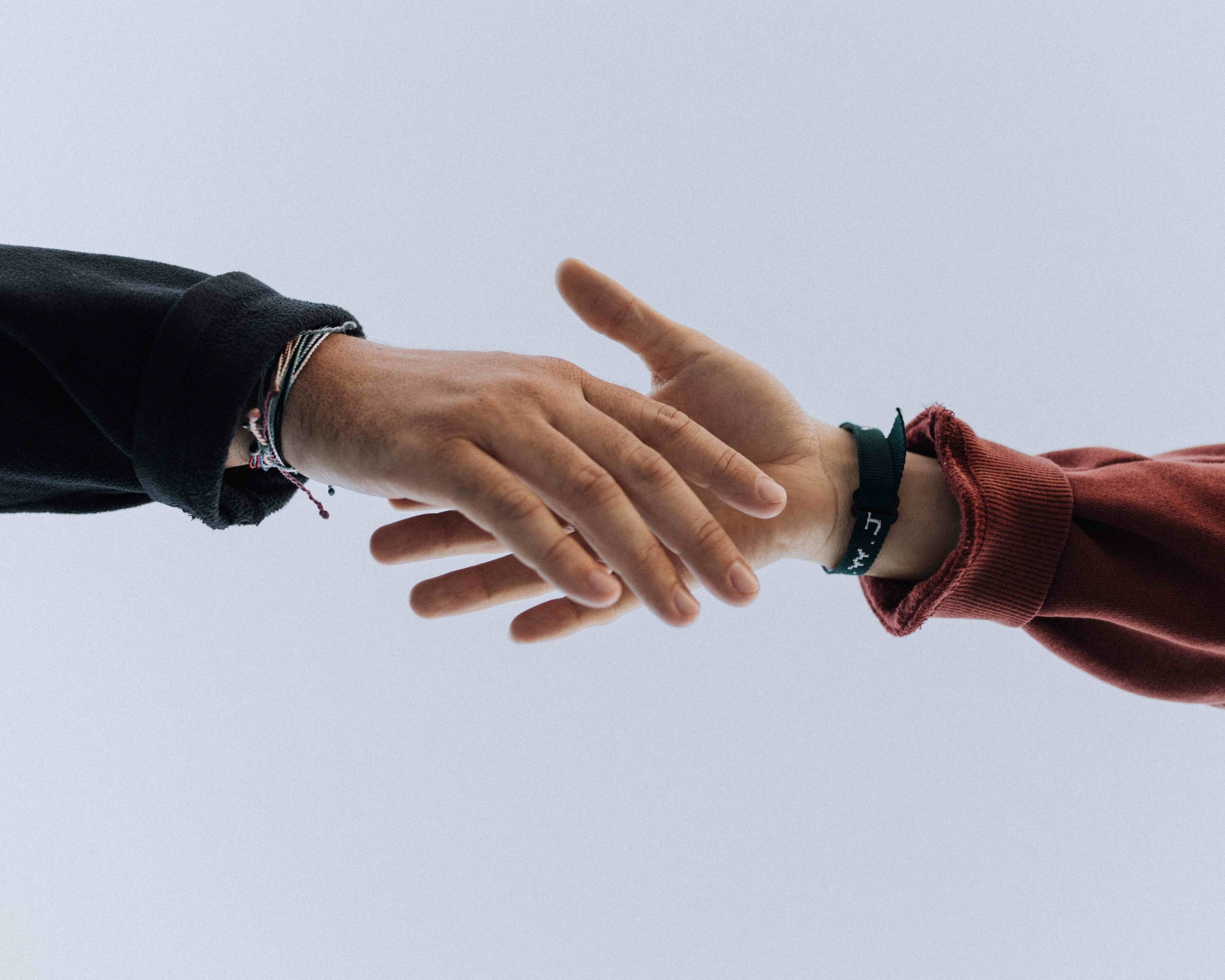 två händer som sträcker sig mot varandra
